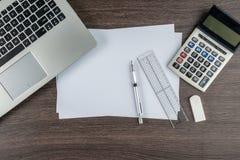 Ordinateur portable, calculatrice de papier de règle de stylo et gomme sur le bureau de travail Photographie stock libre de droits