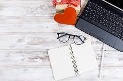 Ordinateur portable, carnet et cadeau avec le coeur sur la table en bois Image libre de droits
