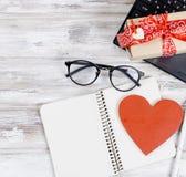 Ordinateur portable, carnet et cadeau avec le coeur sur la table en bois Photographie stock