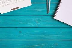 Ordinateur portable, carnet et crayons sur le fond en bois de turquoise avec Photographie stock
