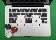 Ordinateur portable, cartes de tisonnier et jetons de poker Photo libre de droits