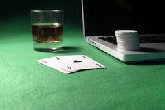 Ordinateur portable, cartes de tisonnier et jetons de poker Images stock