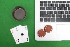 Ordinateur portable, cartes de tisonnier et jetons de poker Image stock