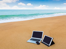 Ordinateur portable, comprimé et smartphone sur la plage dans l'heure d'été Photographie stock