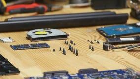 Ordinateur portable démontant dans l'atelier de réparations, plan rapproché Carte mère démontée d'ordinateur sur le lieu de trava banque de vidéos
