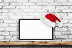 Ordinateur portable d'écran vide sur le mur de briques blanc avec le chapeau de Noël Photos libres de droits