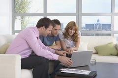 Ordinateur portable d'And Couple With d'agent de Real Estate dans la nouvelle maison Photographie stock libre de droits