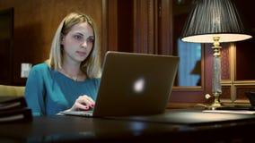 Ordinateur portable d'ouverture de femme d'affaires pour travailler au bureau avec la lampe de table banque de vidéos