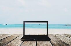 Ordinateur portable d'ordinateur sur la table en bois avec le fond de vue de plage Chemin de coupure sur l'écran Photos libres de droits