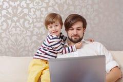 Ordinateur portable d'utilisation d'homme et de garçon photo libre de droits