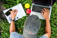 Ordinateur portable d'utilisation d'homme sur l'herbe Photo libre de droits