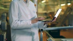 Ordinateur portable dans les mains femelles d'un travailleur d'usine banque de vidéos