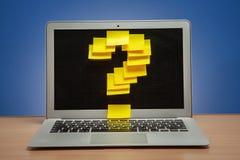 Ordinateur portable dans les rappels des autocollants jaunes sous forme de symbole de point d'interrogation sur la table avec le  Images stock