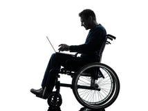 Ordinateur portable de calcul handicapé d'homme dans le silhoue de fauteuil roulant Photo libre de droits