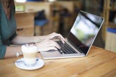 Ordinateur portable de dactylographie en café Image libre de droits
