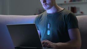 Ordinateur portable de dactylographie de soldat professionnel regardant la caméra, connexion internet, travail banque de vidéos