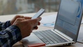 Ordinateur portable de dactylographie de téléphone d'homme de communication d'affaires banque de vidéos