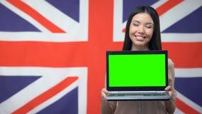 Ordinateur portable de représentation femelle avec l'écran vert sur le fond britannique de drapeau, étude banque de vidéos