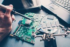 Ordinateur portable de soudure de technicien-réparateur PL in FR has S on both words de disposition de carte PCB photo stock