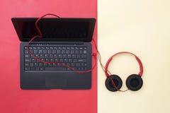 Ordinateur portable et écouteurs reliés sur un fond coloré Photo stock