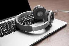Ordinateur portable et écouteurs sur une table photographie stock libre de droits