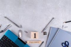 Ordinateur portable et approvisionnements, calendrier en bois avec date le 1er septembre sur un bureau concret gris Images libres de droits