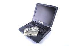 Ordinateur portable et argent d'isolement Photos stock