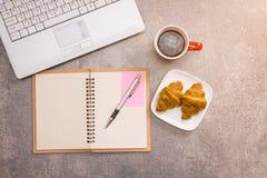 Ordinateur portable et carnet avec la tasse de café et le croissant Image stock