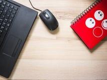Ordinateur portable et carnet rouge sur la table le jour ouvrable Photographie stock