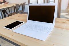 ordinateur portable et comprimé blancs de lieu de travail de bureau sur la table en bois en m Image stock