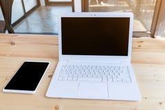 ordinateur portable et comprimé blancs de lieu de travail de bureau sur la table en bois en m Image libre de droits