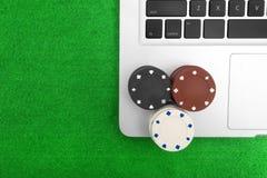 Ordinateur portable et jetons de poker Images stock