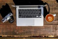Ordinateur portable et Latte d'appareil-photo sur la surface en bois dehors photos stock