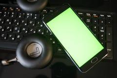 Ordinateur portable et smartphone d'écouteurs avec l'écran vert Photos stock