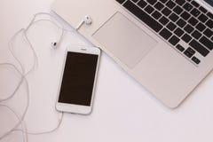 Ordinateur portable et téléphone avec des écouteurs sur une table Plan rapproché le dessus luttent photo stock