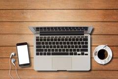Ordinateur portable et téléphone intelligent sur la table en bois Photographie stock libre de droits