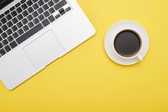 Ordinateur portable et tasse de café sur le fond jaune Photo stock