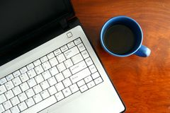 Ordinateur portable et une tasse de café bleue sur une table Photographie stock