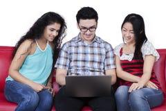 Ordinateur portable ethnique multi d'utilisation d'étudiant sur le sofa Photo libre de droits