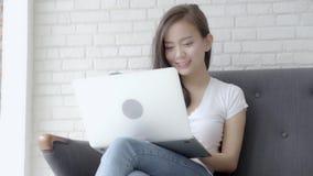Ordinateur portable fonctionnant de belle jeune femme asiatique de portrait avec le sourire se reposant sur le divan au salon
