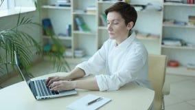 Ordinateur portable fonctionnant de bureau spacieux de fille d'employé de bureau banque de vidéos