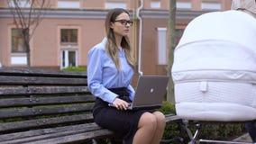 Ordinateur portable fonctionnant de femme regardant la mère avec le chariot passant par, rêvant du bébé banque de vidéos