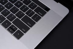 Ordinateur portable gris en métal sur la fin noire de fond  Vue de ci-dessus sur le clavier Image libre de droits