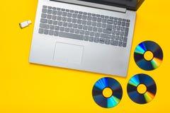 Ordinateur portable, lecteurs de cd-rom, commande d'instantané d'USB sur un fond jaune Media numérique moderne et périmé photos stock