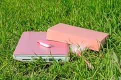 Ordinateur portable, livre, stylo et disque roses sur la clé sur l'herbe verte Image libre de droits