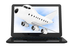Ordinateur portable moderne avec la bande dessinée Toy Jet Airplane Flying  Photos stock