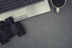 Ordinateur portable ou carnet, binoculaire et tasse de café sur le travail Image libre de droits