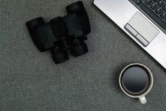 Ordinateur portable ou carnet, binoculaire et tasse de café sur le travail Image stock