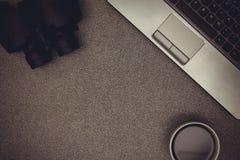 Ordinateur portable ou carnet, binoculaire et tasse de café sur le travail Photo stock