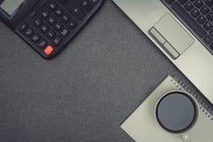 Ordinateur portable ou carnet, calculatrice et tasse de café sur le wor Image libre de droits